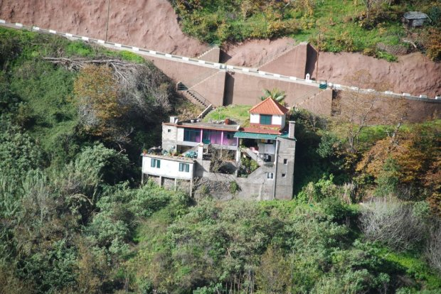 House at base of cliff.